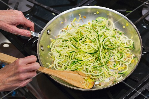 Gluten-free courgette spaghetti being cooked in a pan on the stove
