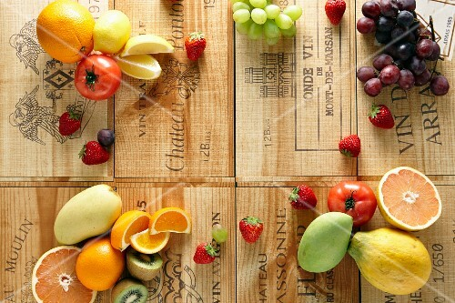 Various fruits and tomatoes on wine crates