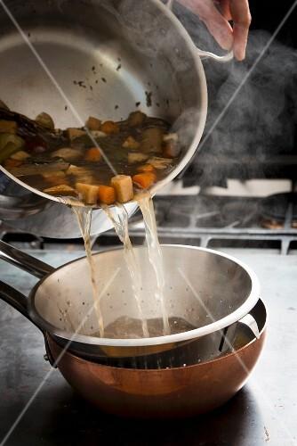 Broth being sieved