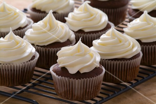 Chocolate cupcakes with cream cheese frosting on a cooling rack