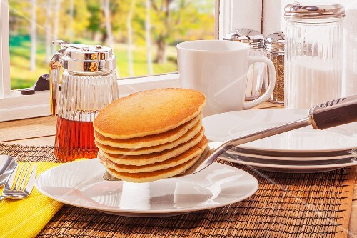 Buttermilk pancakes and maple syrup on a table next to a window