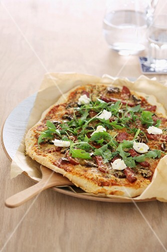 A pizza topped with bacon, rocket and mozzarella cheese