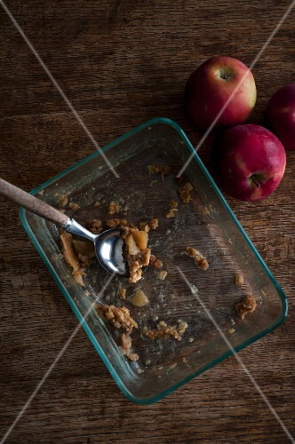 The remains of apple crumble in a glass baking dish