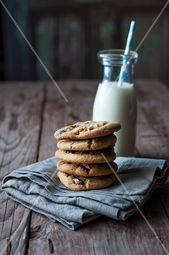 A stack of chocolate chip cookies on a tea towel with a bottle of milk