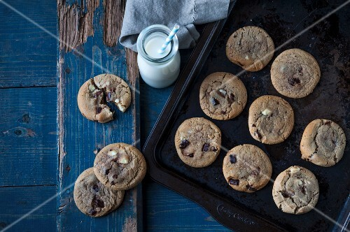 Chocolate chip cookies on a baking tray next to a bottle of milk