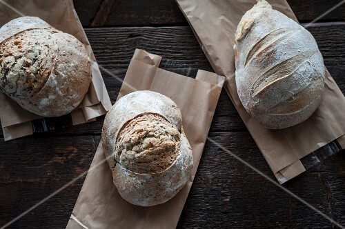 Three loaves of bread on paper bags