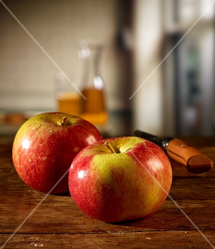 Red apples on a wooden table and apple juice in the background