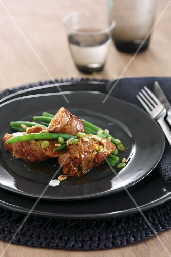 Sausages wrapped in bacon on green beans with pine nuts and spring onions