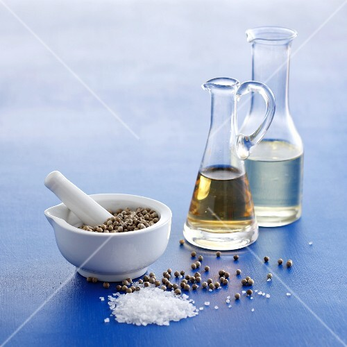 An arrangement of vinegar and oil in carafes with peppercorns and sea salt in a mortar