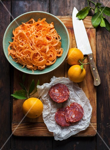 Grated carrots, sausage and oranges on chopping board