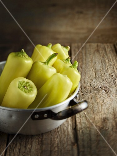 Yellow pointed peppers in an aluminium pot on a wooden table