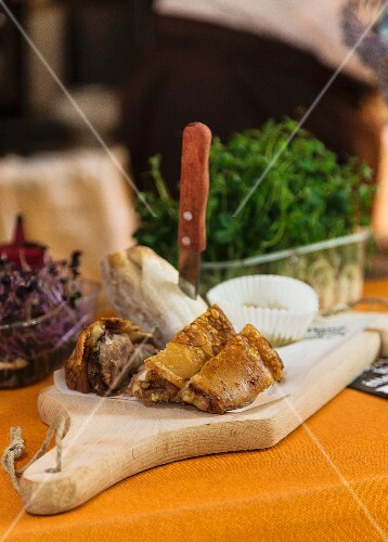 Pork knuckle and a bread roll on a chopping board