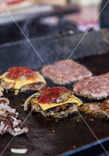 Cheeseburgers with ketchup on a gastro grill