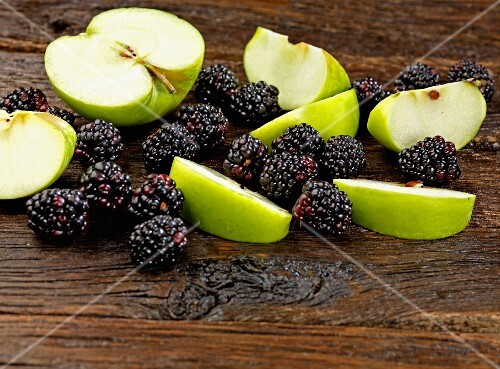 Apples and blackberries on a wooden surface