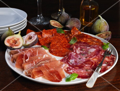 A platter of cold cuts with figs and basil