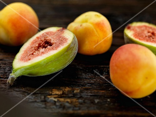 Figs and apricots on a wooden surface