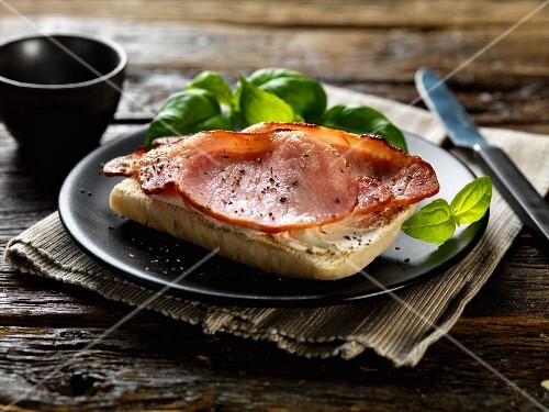 Smoky bacon with syrup, cream cheese and basil on ciabatta bread