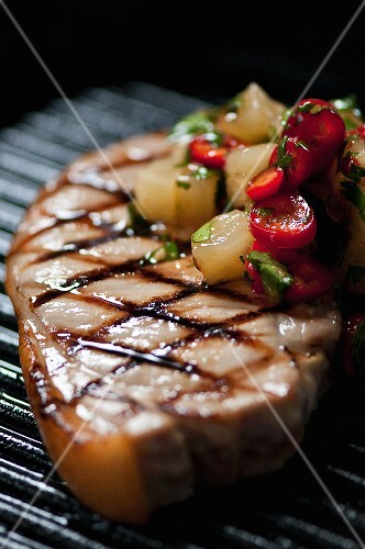 A grilled pork chop with a pineapple and chilli salsa