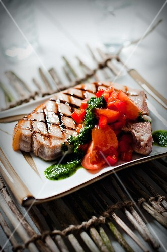 A grilled pork chop with red salsa and pesto sauce