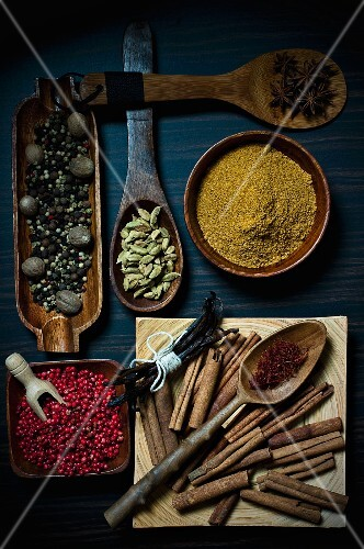 Various spices on wooden spoons and in wooden bowls