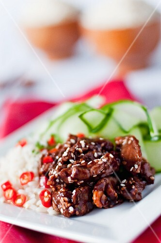 Beef in hoi-sin sauce with roasted sesame seeds served with rice with chilles and a cucumber salad