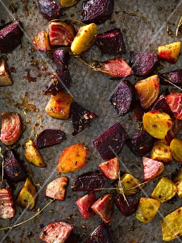 Various types of beets roasted with herbs on a baking tray (seen from above)
