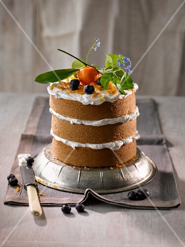 A triple layer mini cake with a cream filling garnished with ornamental oranges