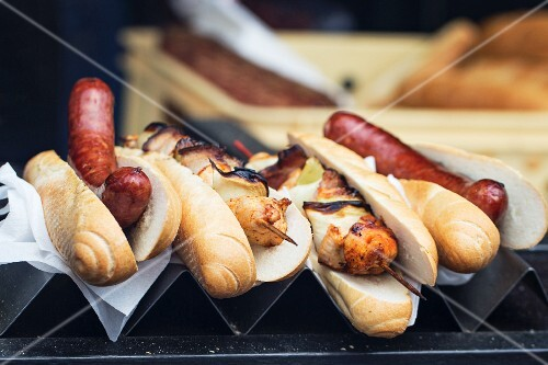 Hot dogs and grilled chicken skewers on a metal stand in a fast food shop