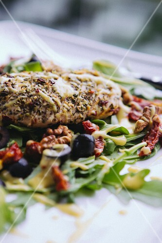 Grilled chicken on a rocket salad with dried tomatoes, olives and walnuts