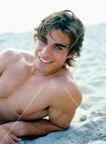 A young, smiling, topless man lying on a beach