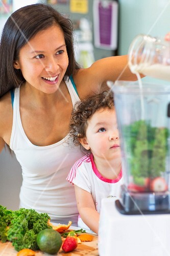 A woman mixing a smoothie for a little girl in a kitchen