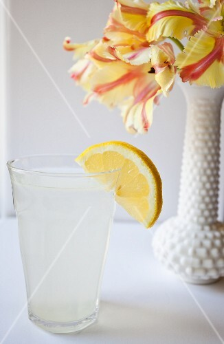 A glass of lemon water next to a vase of flowers