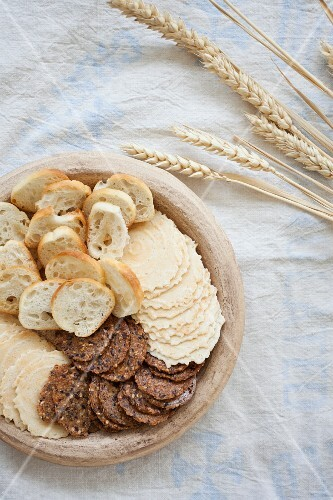 Various wheat crackers sitting in a stoneware bowl next to dried wheat ears