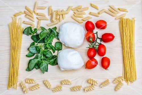 An arrangement of Italian food (pasta, basil, mozzarella and tomatoes)
