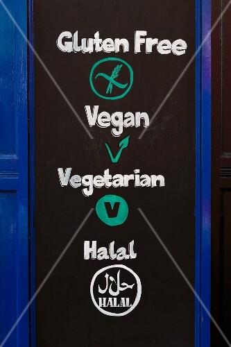 A restaurant sign with the words 'Gluten Free', 'Vegan', 'Vegetarian' & 'Halal'