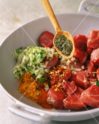 Diced meat being mixed with herbs, spices and onions