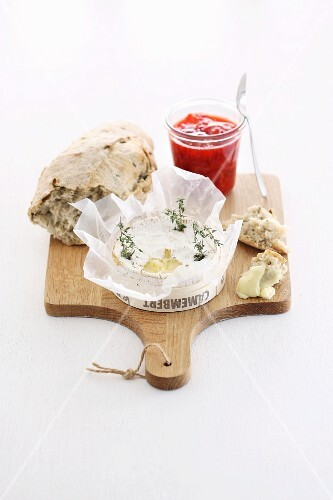 Camembert with thyme, bread and chutney on a chopping board