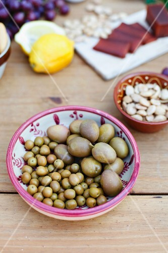 Two types of green olives in a ceramic bowl