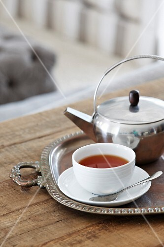 Teacup and silver teapot on tray on rustic wooden table