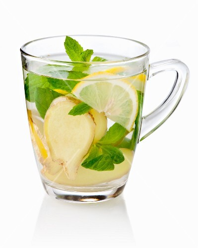 Ginger tea with fresh ginger, mint and lemon in a glass cup