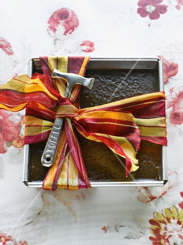 Toffee in a metal tin with a bow and a toffee hammer