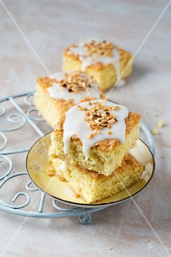 Slices of vanilla cake with icing and hazelnuts