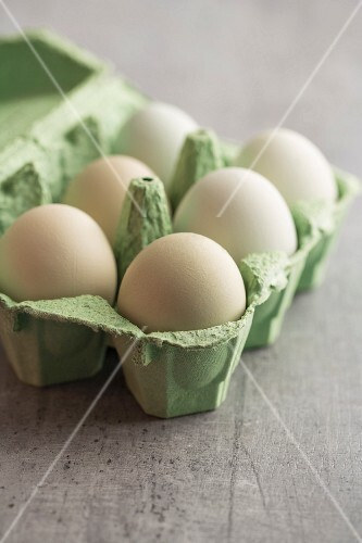 Hen's eggs with green shells in an egg box