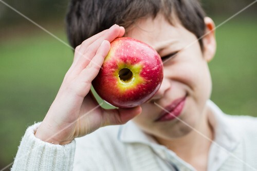 A little boy looking through a cored apple