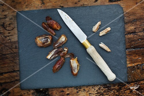 Halved and pitted Halawi dates with a knife on a chopping board