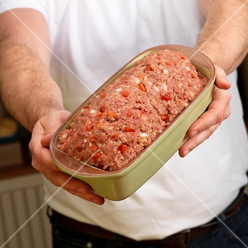 Hands holding raw Mexican meat loaf in green ceramic baking dish