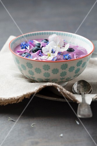 Blueberry yoghurt with blueberries and edible flowers