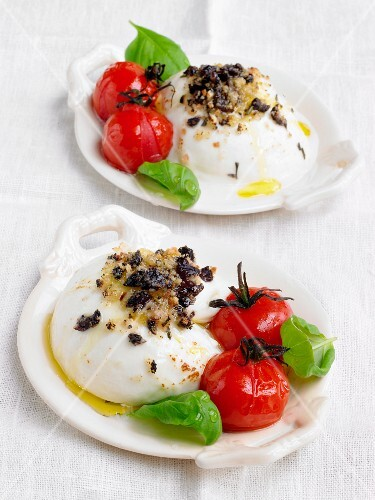 Baked mozzarella with olive crumbs, tomatoes and basil