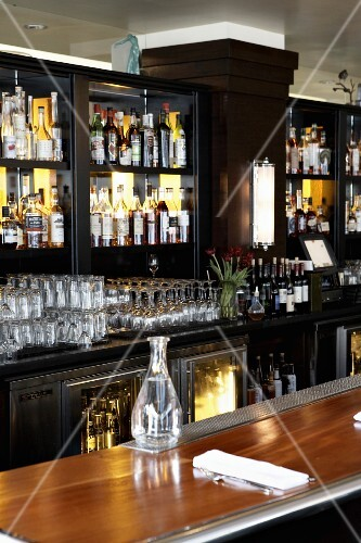 A polished wooden bar in a restaurant with shelves of spirits and glasses behind it