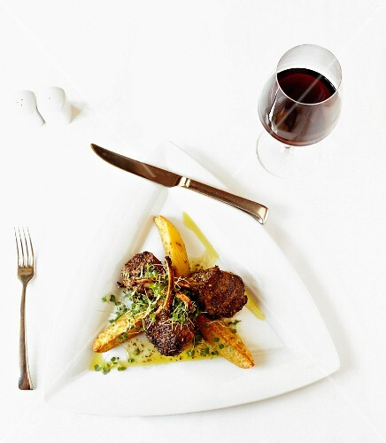 Grilled lamb chops with herbs, bean sprouts and potato wedges (seen from above)